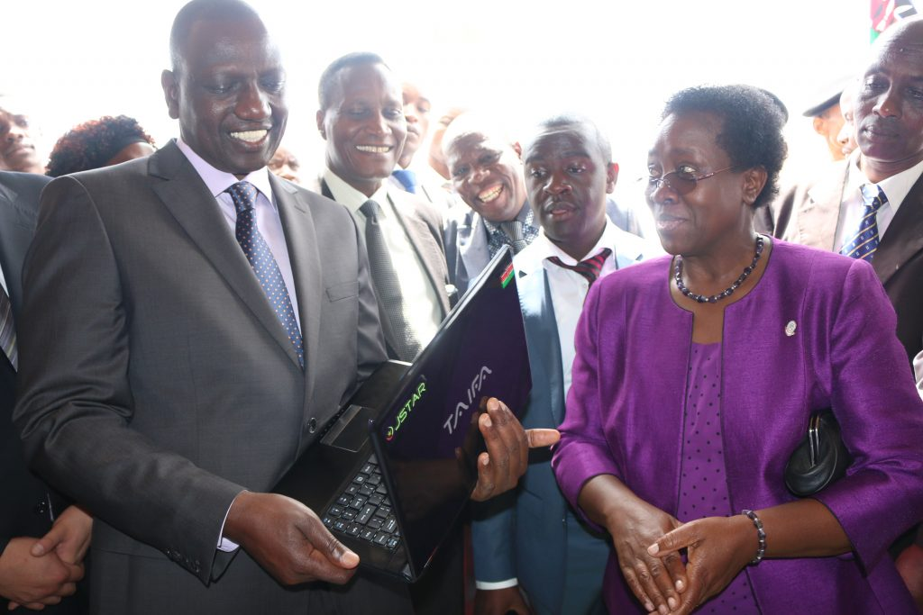 The Deputy President, Hon. William Ruto examines the JKUAT made Taifa Laptop as Calvin Kebati and the Vice Chancellor looks on. The laptop is a product of the NITP.