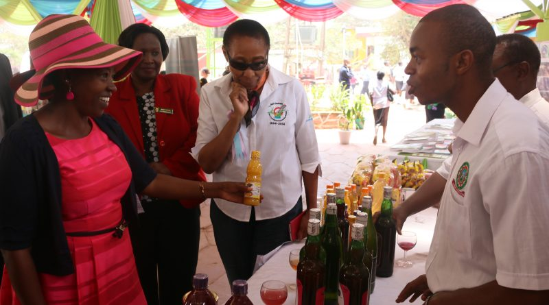 A JKUAT Food Science exhibitor explains to Mrs. Ruto how value addition of various food products such as juice, yoghurt, wine and jam is done at JKUAT.
