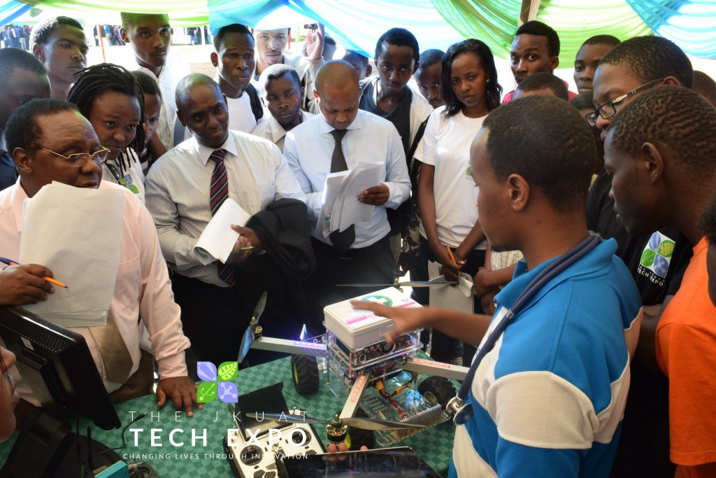 Judges and attendees follow explanations of an exhibitor at the JKUAT Tech Expo.