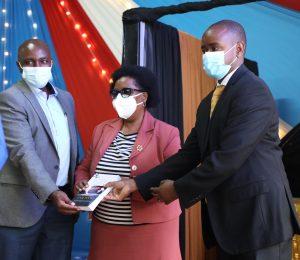 Dr. Patrick M. Mburugu (left), Prof. Victoria Ngumi (center) and Dr. Justus M. Simba (left) showcase the Victoria Pediatrics Case Book