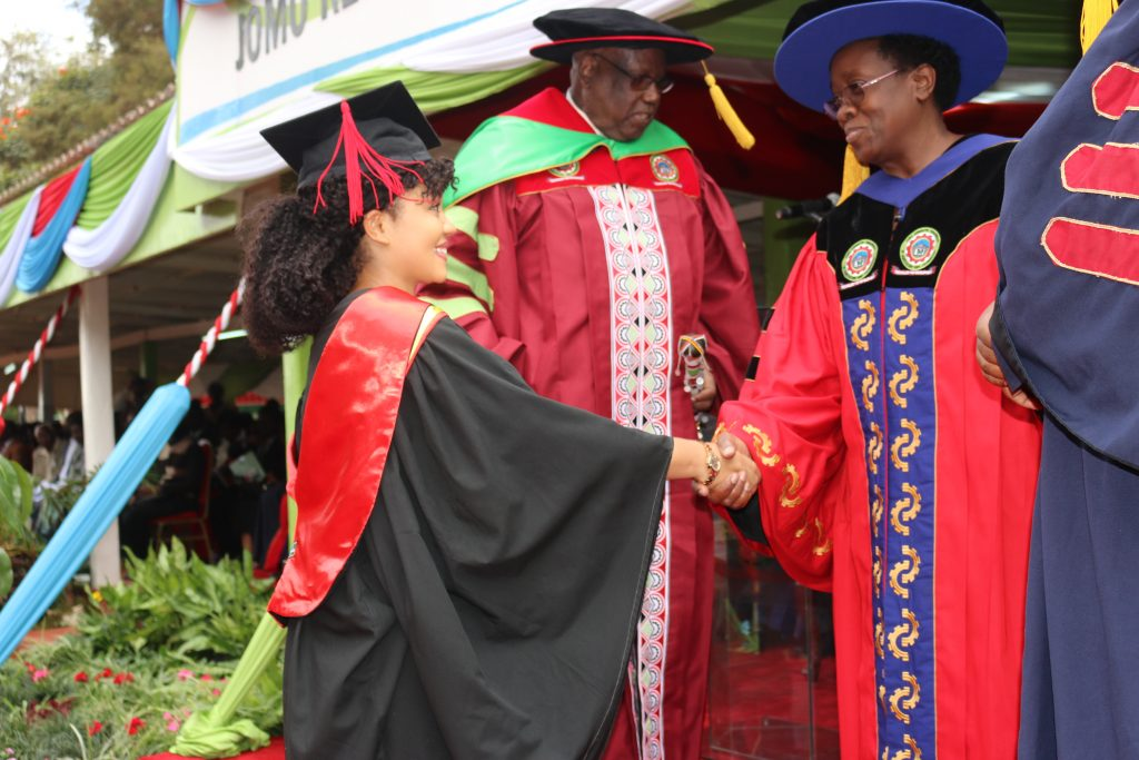 Ms. Mawo shakes hands with the Vice Chancellor Prof. Mabel Imbuga after being conferred with her Degree by the Chancellor, Prof. Ole Maloiy