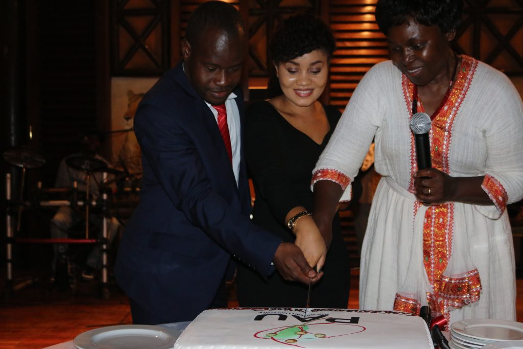 Mr. Hastings Simbarashe, aka 'Simba', Ms. Nathalie Suliy and the Dean of Students Ms. Emma Omulokoli cutting the PAU cake to celebrate their graduation at the dinner.