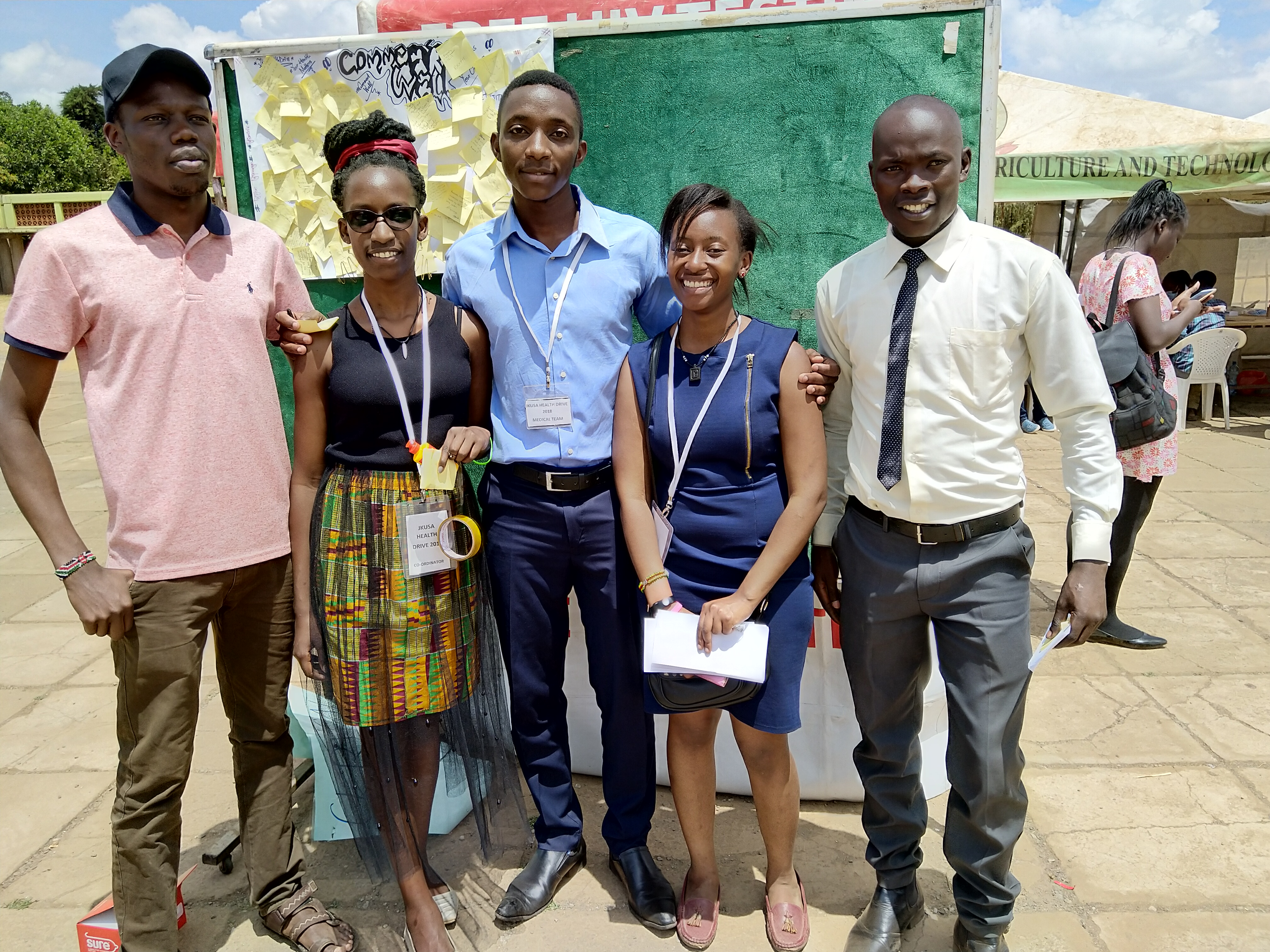 Ms. Claire poses with part of her team at the pavilion on the last day of the drive. Behind them is the comment/feedback board.